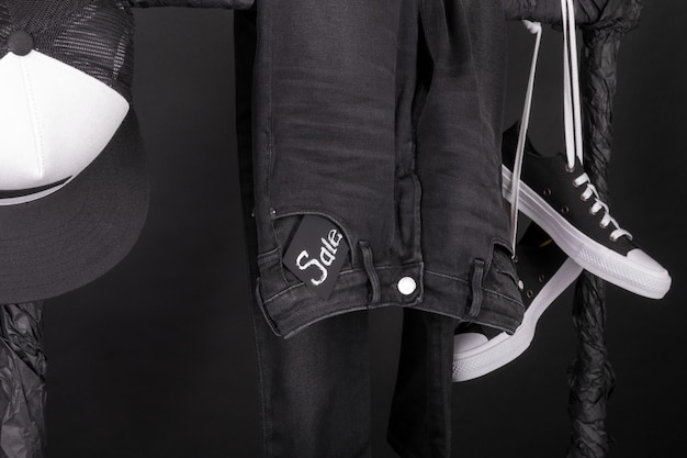Snaekers preto e branco, boné e calça, jeans pendurado no rack de roupas. Foto Premium