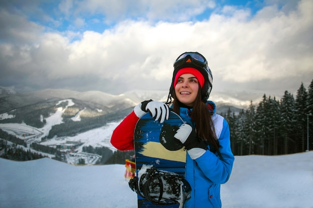 Snowboarder alegre mulher no inverno na estação de esqui Foto Premium