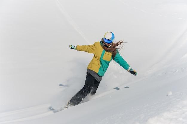 Snowboarder feminino no sportswear colorido e capacete descendo a colina de neve em pó Foto Premium