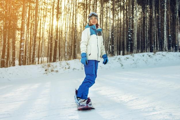 Snowboarder feminino snowboard na montanha Foto Premium