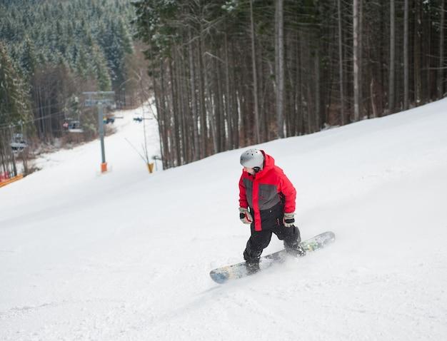 Snowboarder masculino desliza da montanha em dia de inverno, com vista para a encosta nevada e floresta em um resort de inverno Foto Premium