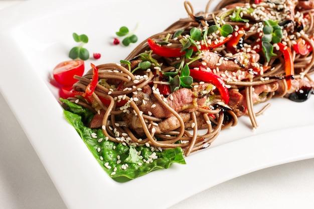 Soba macarrão de trigo sarraceno com fatias de carne, legumes frescos e molho de soja, cozinha asiática Foto Premium