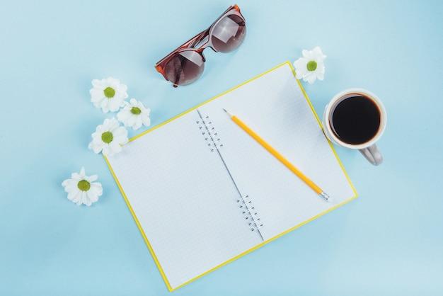 Sobre o caderno azul lápis, régua e flores brancas Foto Premium