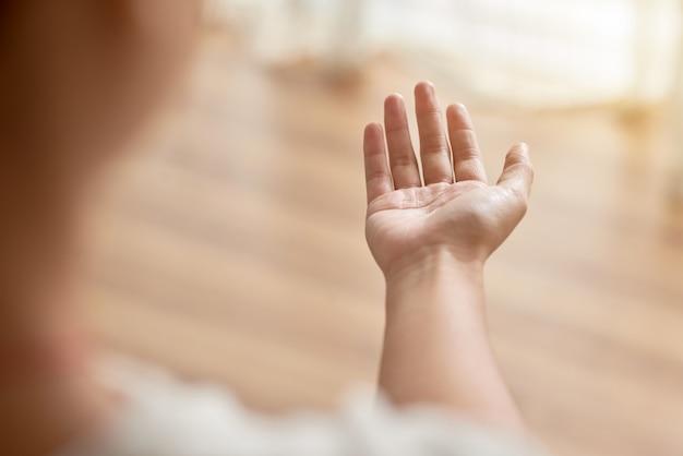 Sobre o ombro da mão da pessoa irreconhecível, esticada para a frente, implorando por ajuda Foto gratuita