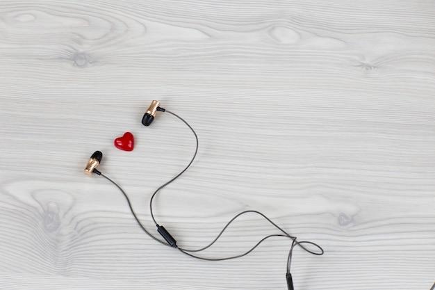 Sobre um fundo claro de madeira, fones de ouvido e um coração vermelho Foto Premium