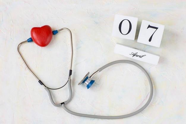 Sobre um fundo claro, um steakscope e um coração vermelho e uma data do calendário de 7 de abril Foto Premium