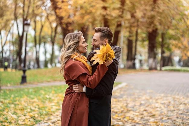 Sobre uma foto de beijo. marido e mulher se abraçaram, sorrindo, olhando um para o outro no parque de outono. exterior Foto Premium