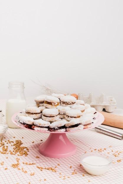 Sobremesa açucarada fresca empilhados no carrinho do bolo com ingredientes contra a parede branca Foto gratuita