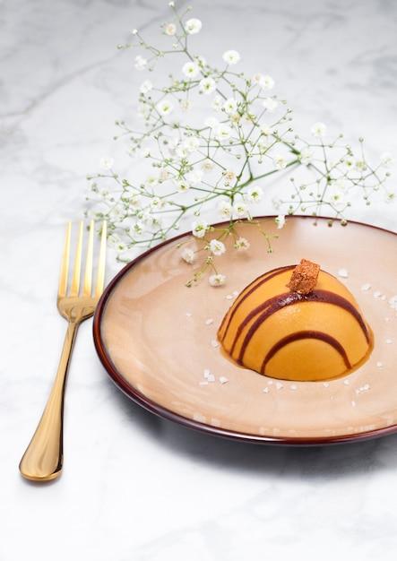 Sobremesa de caramelo restaurante de luxo no prato com garfo de ouro e flores Foto Premium