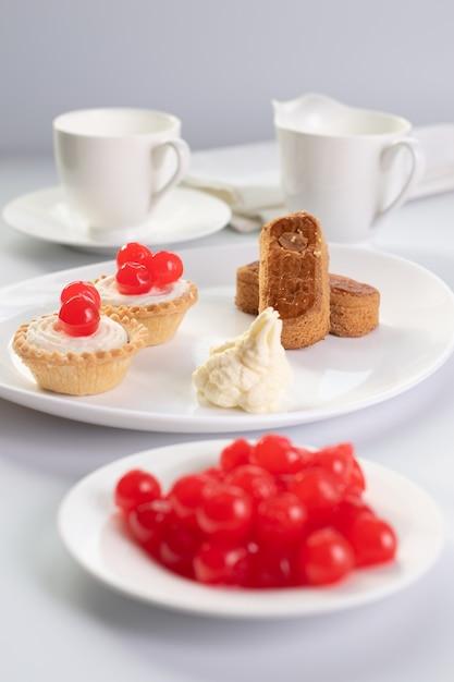Sobremesa de cerejas com rodelas de amêndoa e dois cestos Foto Premium