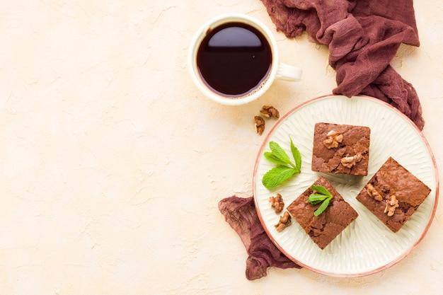 Sobremesa de chocolate doce brownie com nozes e significou folhas no prato de ofício e copo Foto Premium