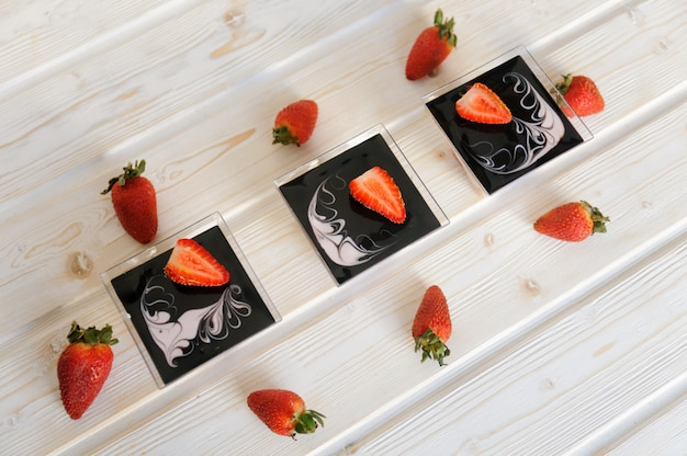 Sobremesa de creme em um copo com morangos frescos em fundo branco Foto Premium