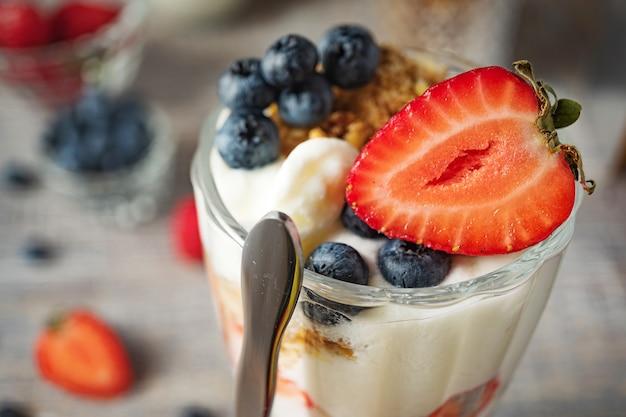 Sobremesa de leite com morangos e mirtilos close-up Foto Premium