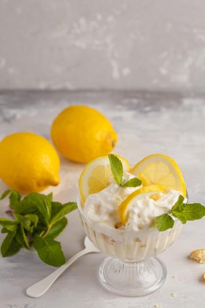 Sobremesa de limão. bolinho de limão inglês, cheesecake, chantilly, parfait. musse do fruto no vidro em um fundo claro. Foto Premium