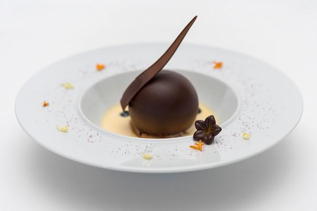 Sobremesa de luxo com chocolate globo e molho de baunilha, servido em um biscoito, com chocol Foto Premium