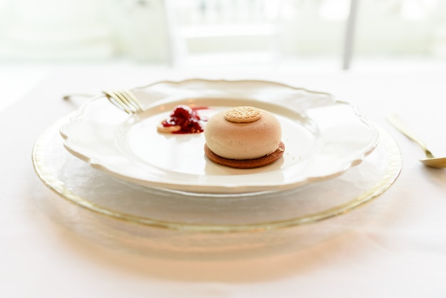 Sobremesa de sorvete com biscoito e geléia de frutas vermelhas elegantemente apresentada com talheres de ouro Foto Premium