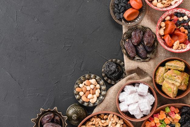Sobremesa do ramadã tradicional e nozes em tigela metálica e barro no pano de fundo preto Foto gratuita