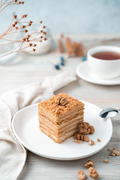 Sobremesa doce de mel com nozes em um fundo claro suave. vista lateral, orientação vertical. Foto Premium