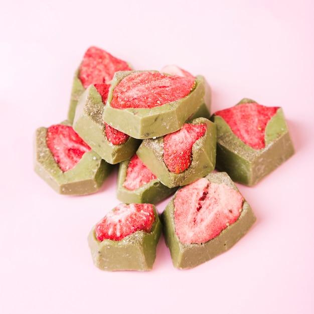 Sobremesa saborosa com morango e chocolate verde sobre fundo rosa Foto gratuita