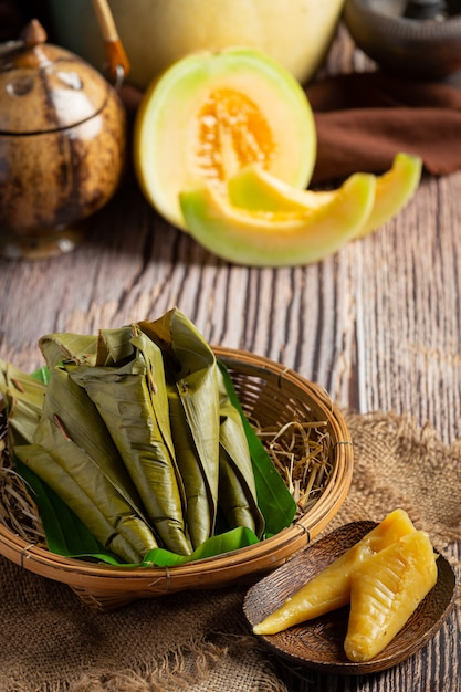 Sobremesa tailandesa. doces de melão cozido no vapor envoltos em casquinha de banana Foto gratuita