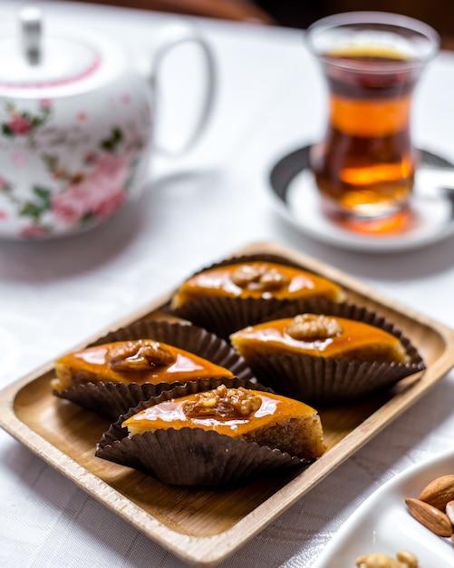 Sobremesa tradicional pakhlava doces com nozes na vista lateral da placa de madeira Foto gratuita