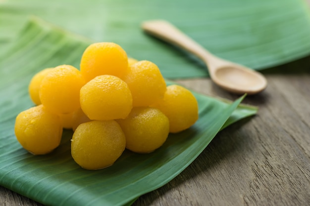 Sobremesas tradicionais tailandesas gemas de ovo de ouro gotas nas folhas de bananeira, mesa superior de madeira Foto Premium