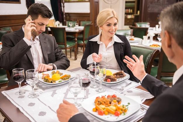 Sócios nos ternos que discutem o contrato durante o almoço de negócio. Foto Premium