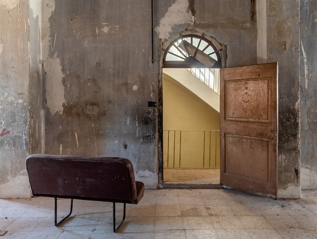 Sofá à falência em frente a uma porta antiga Foto Premium