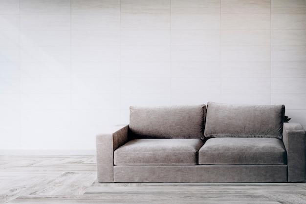 Sofá por uma parede de azulejos Foto gratuita