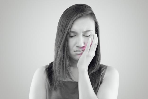 Sofrendo de uma dor de dente, mulher asiática vestindo uma camisa vermelha, sofrendo Foto Premium