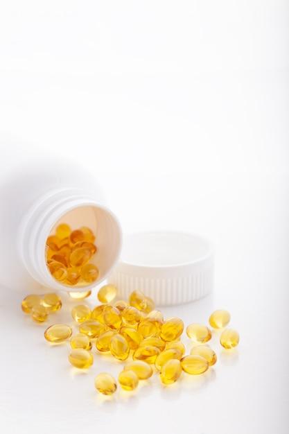 Softgel de óleo de peixe de ouro espalhado da garrafa no fundo branco Foto Premium
