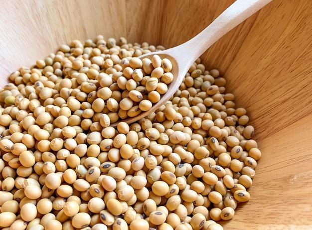 Soja em uma tigela de madeira e colher de pau para colher sementes de soja Foto Premium