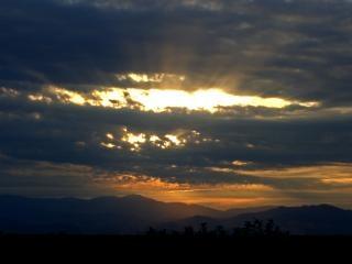 sol brilhando através de nuvens Foto gratuita