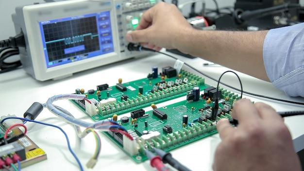 Solda eletrônica manual e teste de osciloscópio Foto Premium