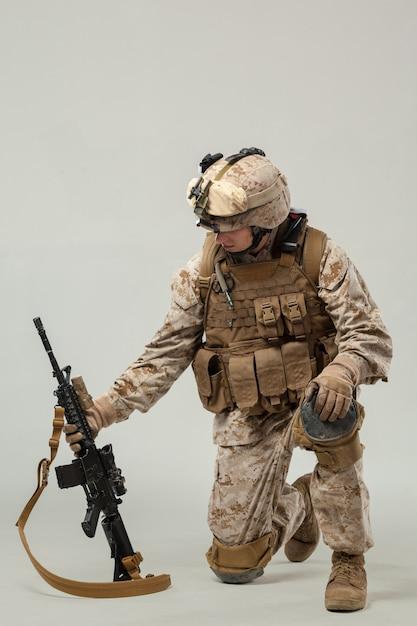 Soldado camuflado segurando rifle Foto Premium