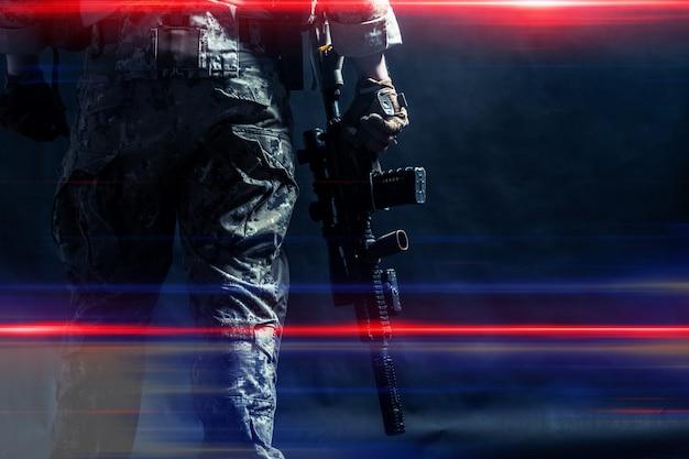 Soldado das forças especiais com rifle na superfície escura Foto Premium