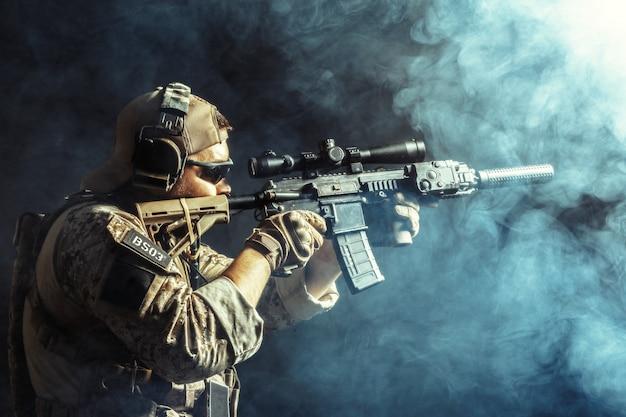 Soldado das forças especiais com rifle no escuro Foto Premium