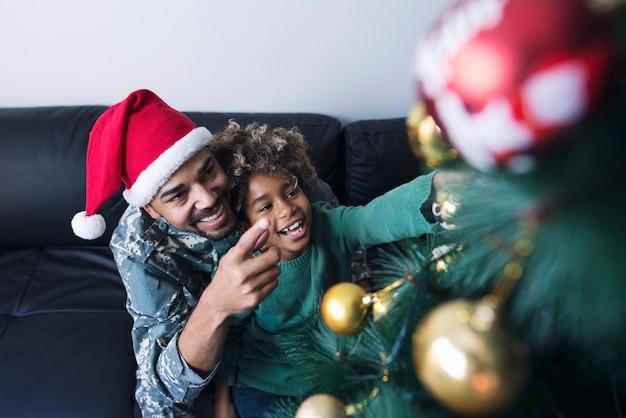 Soldado de uniforme surpreendendo a filha e comemorando o natal juntos Foto gratuita