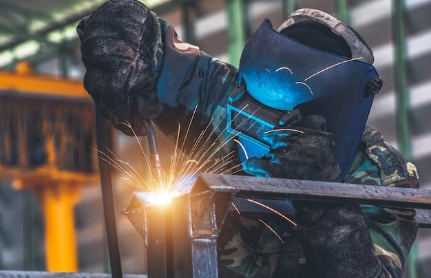 Soldador está soldando peças de metal na fábrica de automóveis Foto Premium