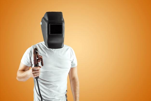 Soldador masculino em um capacete em um fundo laranja. Foto Premium