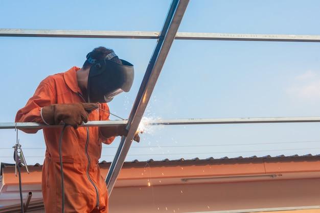 Soldadura de trabalhador na roupa de trabalho alaranjada que solda para a treliça do telhado Foto Premium