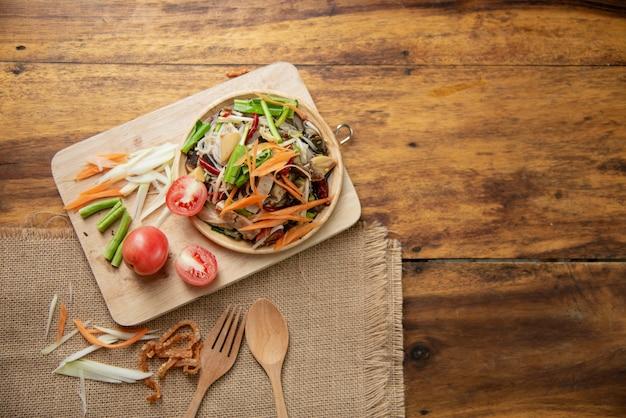 Som tam tailandês, salada de papaia tailandês em fundo de madeira Foto gratuita
