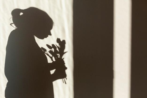 Sombra de mulher segurando flor Foto gratuita