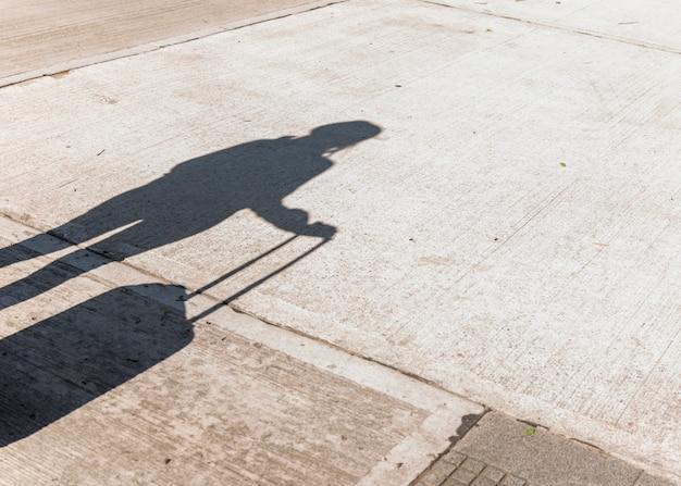 Sombra de uma turista feminina segurando bagagem de rodas no asfalto Foto gratuita