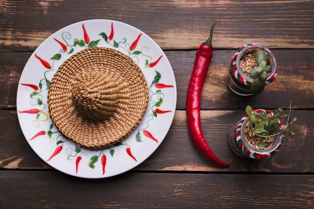 Sombrero na placa perto de plantas em vasos e pimentão Foto gratuita