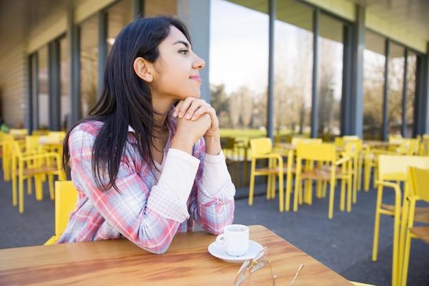 Sonhador bonita jovem desfrutando de beber café no café Foto gratuita
