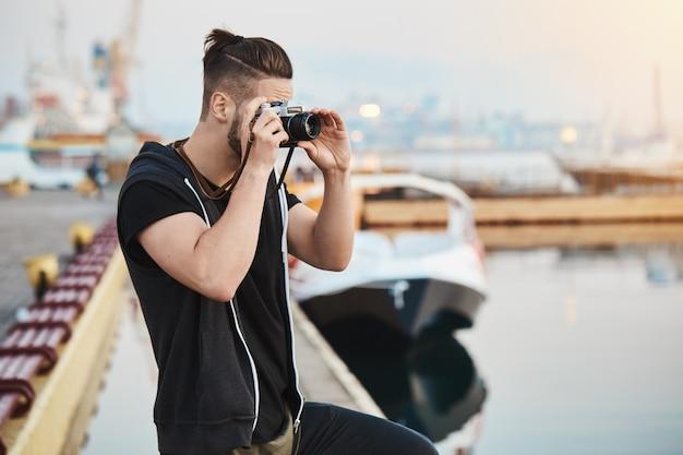 Sonhador fotógrafo europeu criativo com roupa elegante em pé no porto, tirando foto do mar Foto gratuita