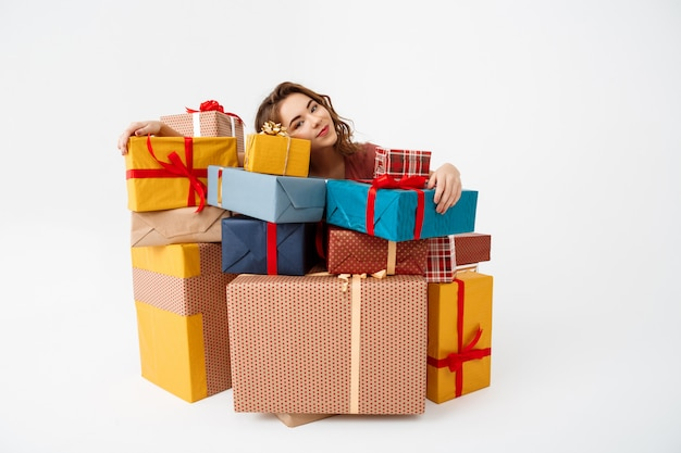 Sonhadora jovem encaracolada entre caixas de presente Foto gratuita