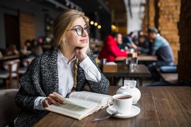 Sonhando a jovem mulher com livro Foto gratuita