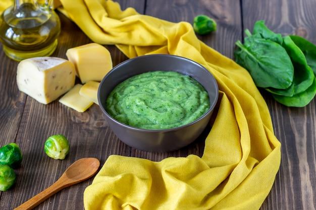 Sopa creme com espinafre e queijo superfície de madeira Foto Premium